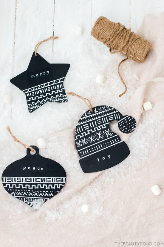 Homemade Mud cloth style ornaments in the shape of an ornament, star and winter hat, hung on pieces of twine.