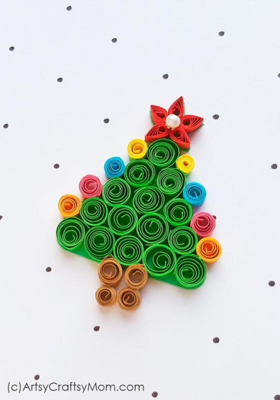 A bright colored paper quilled Christmas tree ornament laying flat on a white piece of paper with polka dots.