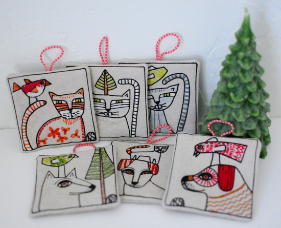 Set of 6 square embroidered ornaments with cats and dogs on the front next to a small wax candle tree.