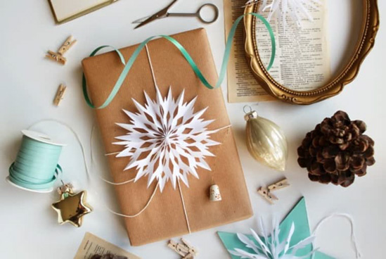 Smalle present wrapped in Kraft paper topped with white string and an ornate paper snowflake surrounded by teal accents, vintage frame, pinecone and golden ornaments.