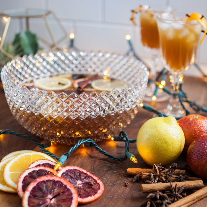 pear and pub ale party punch served in a vintage cut glass punch bowl surrounded by christmas lights