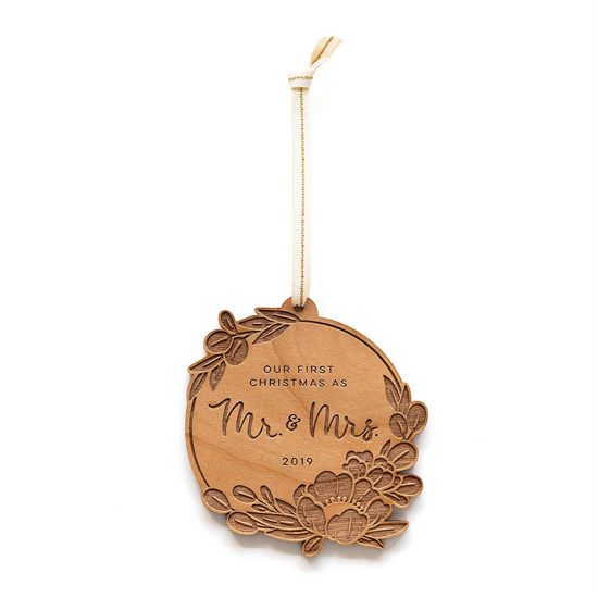 Wooden laser-cut newlywed Christmas ornament on a gold string.