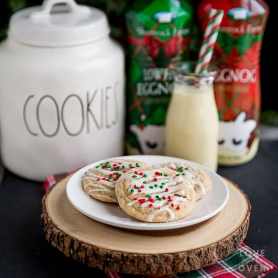 A plate of cookies styled on a wooden round with a cookies jar in the background alongside bottles of eggnog.