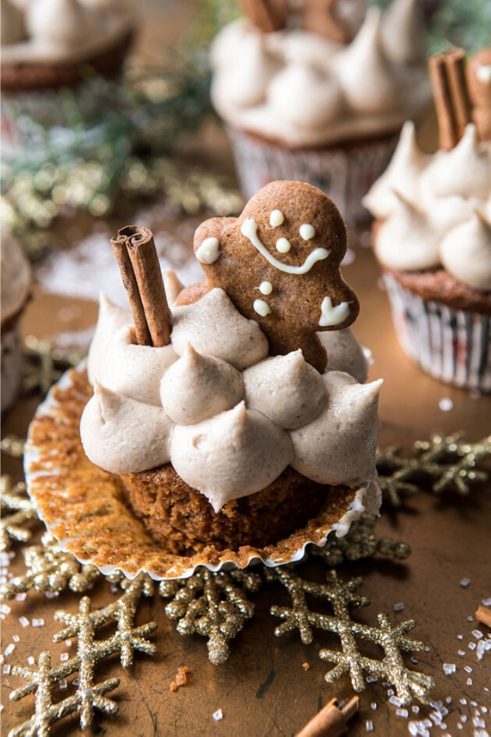 A cupcake with the wrapper pulled back and topped with dollops of frosting, a cinnamon stick and a fresh-baked gingerbread man.