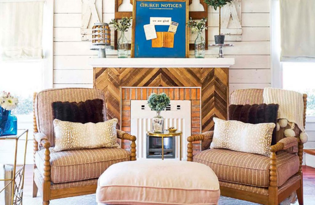 Living room with 2 armchairs and a restored shiplap and brick fireplace.