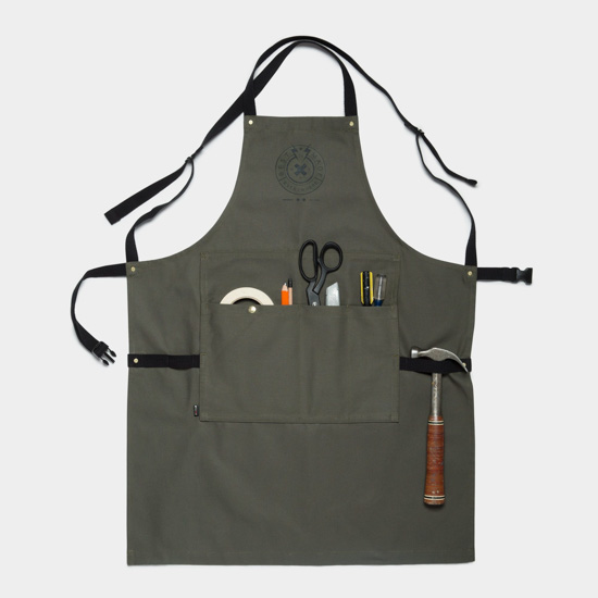 Slate gray utility apron with metal accents and black ribbon ties, pockets filled with scissors, hammer tape and other odds and ends, the perfect guy gift.