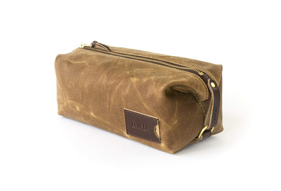 Personalized khaki toiletry bag with leather and zipper accents.