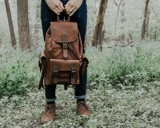 Man standing in the wilderness wearing dark denim and holding a leather backpack.