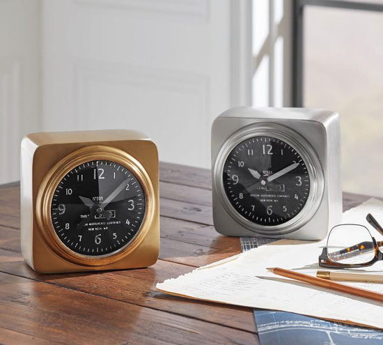 Two aviator alarm clocks now in chrome and one in gold placed on a wooden desk next to paper, pens and glasses.