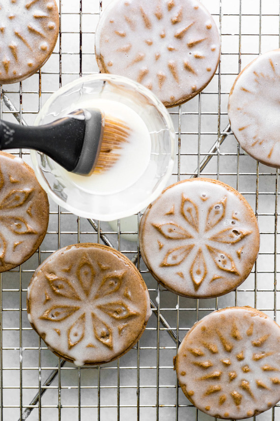 Pastry brush glossing over cookie stamped snowflake gingerbread cookies with white glaze.