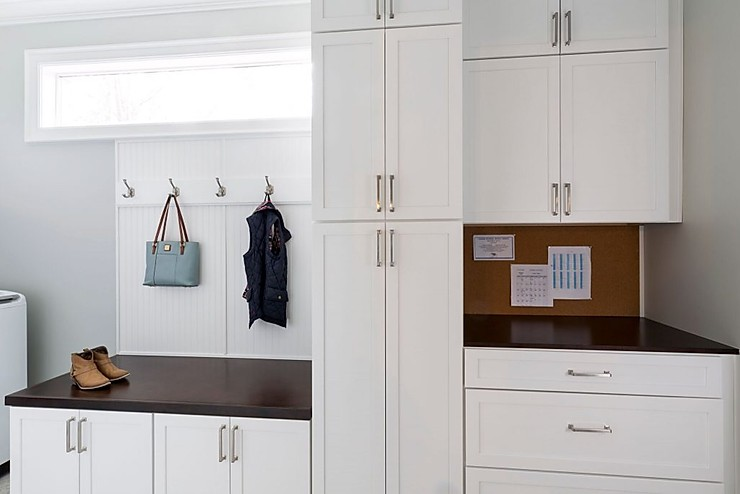 White cabinetry in a customized mudroom with long rectangular window, hanging hooks and cork board.
