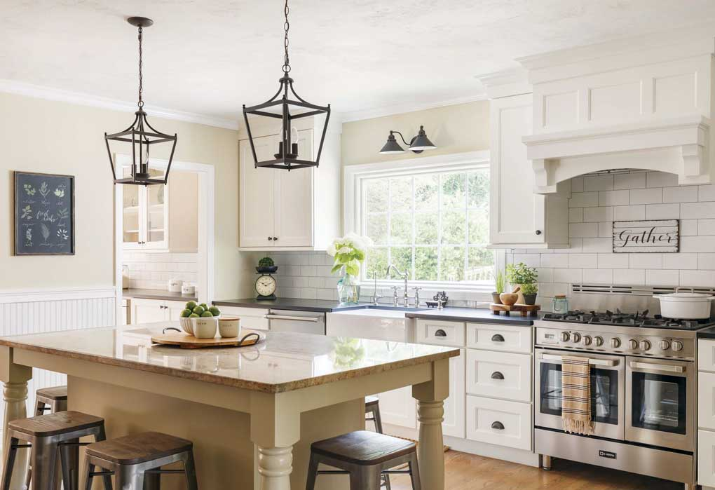Large custom kitchen island with dark pendants hanging above and rustic farmhouse accents throughout the kitchen.