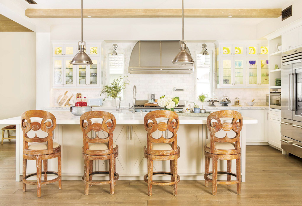 Wide open light colored kitchen looking over the backs of four uniquely carved wooden barstools.