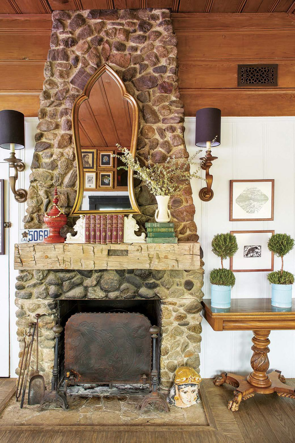 Floor to ceiling stone fireplace with a distressed wooden mantle and a gold-trimmed mirror above it.