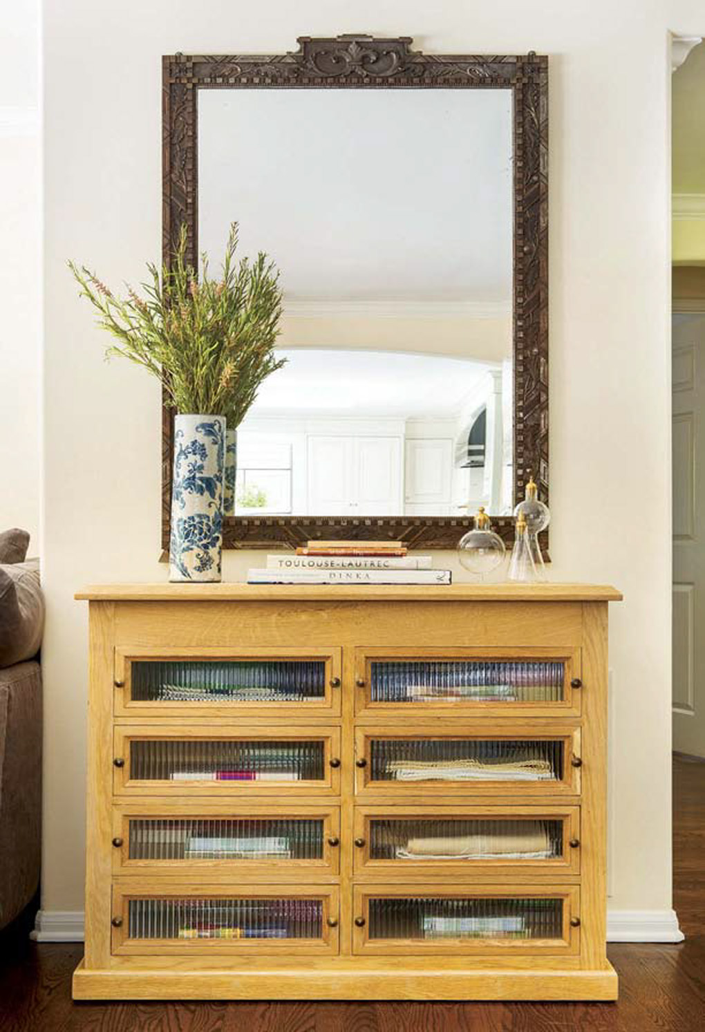Custom made cabinet with muted glass panels topped with an ornate mirror mounted to the wall.