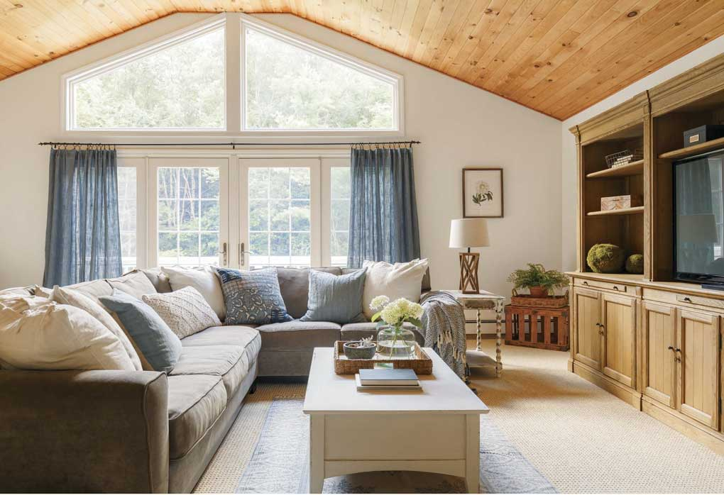 A family room, with a vaulted, wood-paneled ceiling and a large sectional facing a full wall media setup.