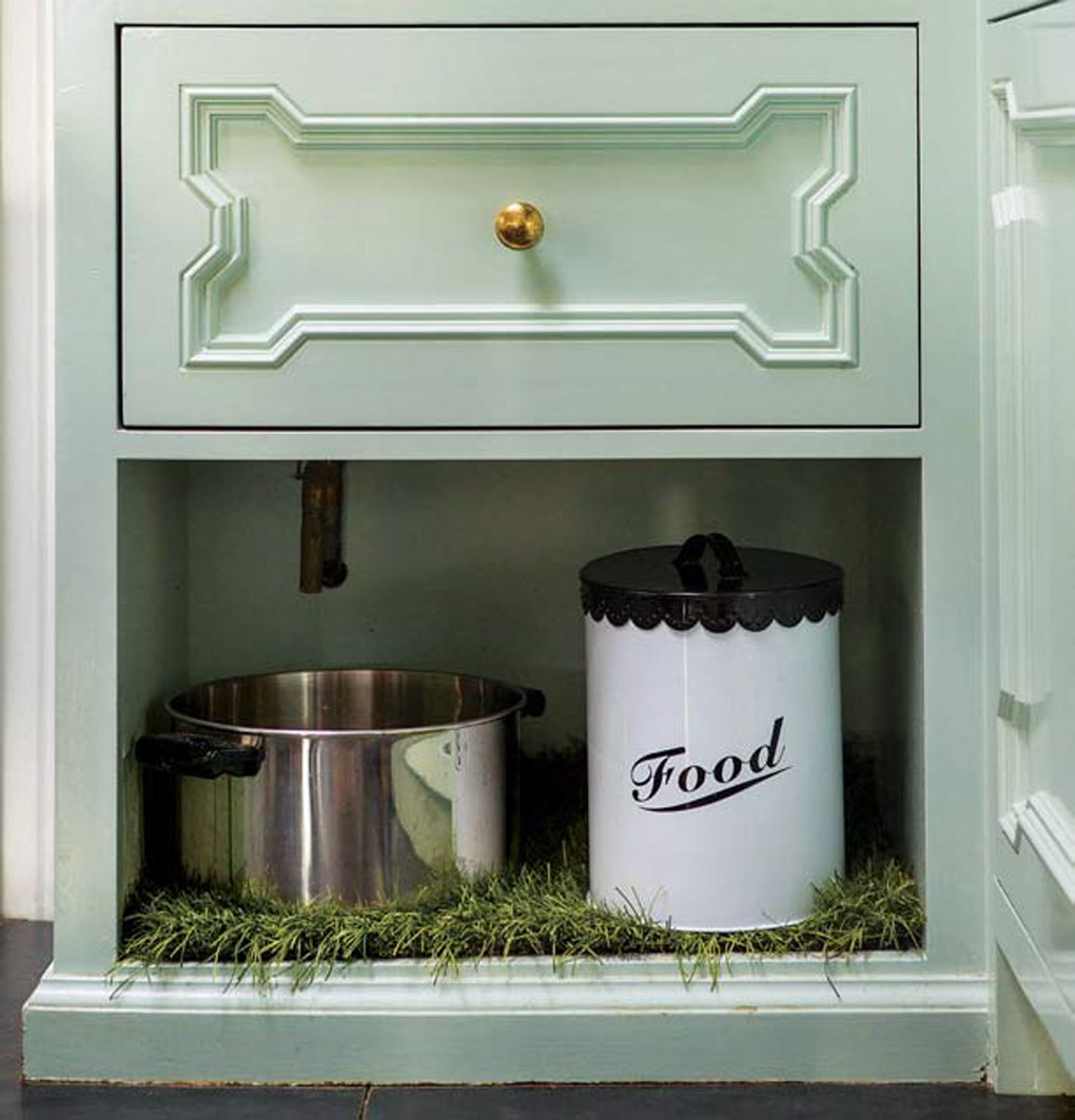 Light aqua kitchen cabinets with a creatively built-in dog feeding station.