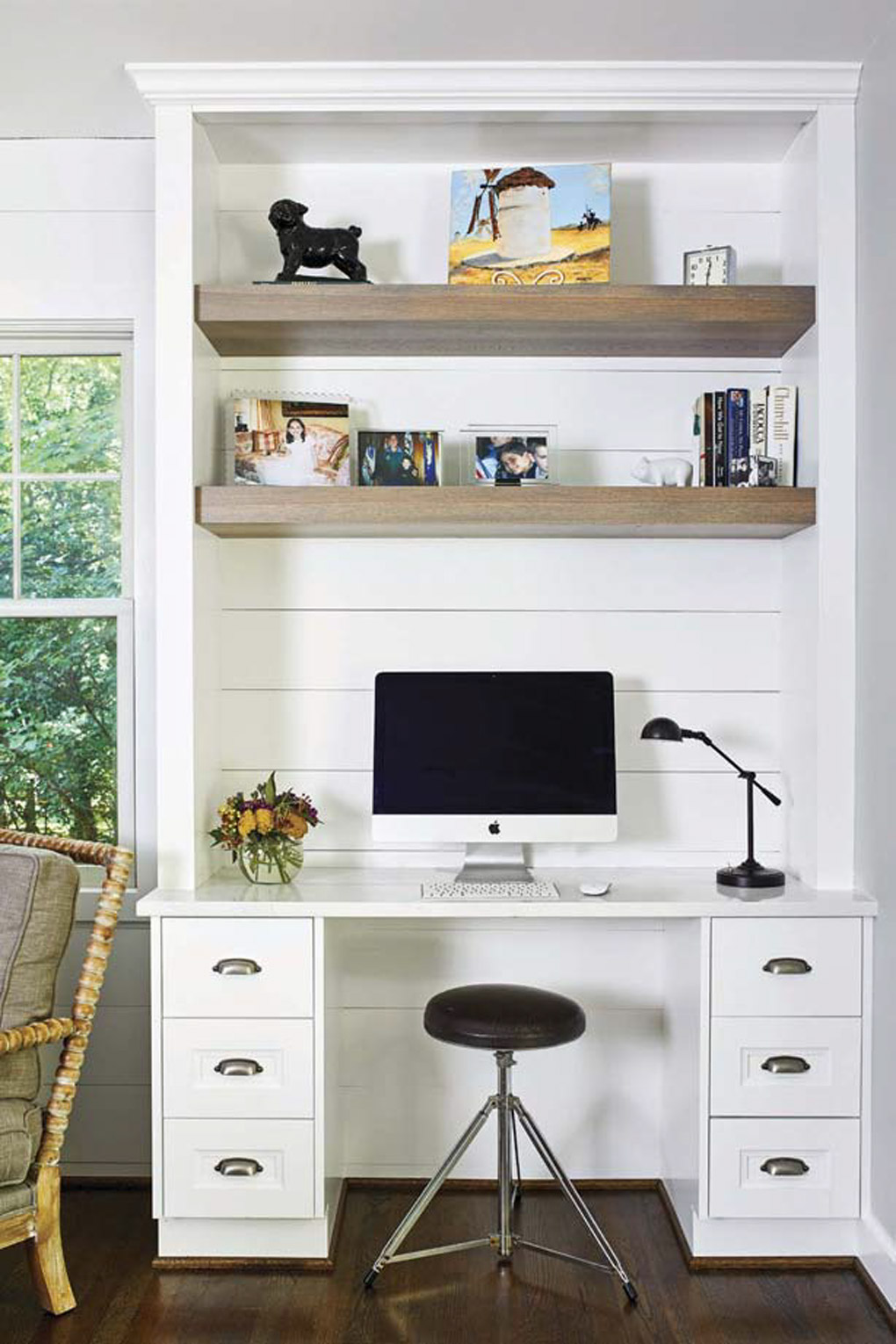 Custom white built-in with shelving, desk and small stool to sit at the computer.