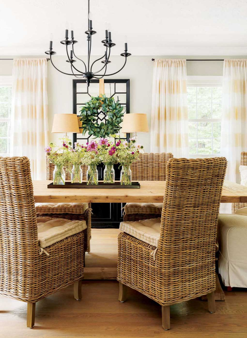 Rustic farmhouse table surrounded by a mix of woven and upholstered chairs.