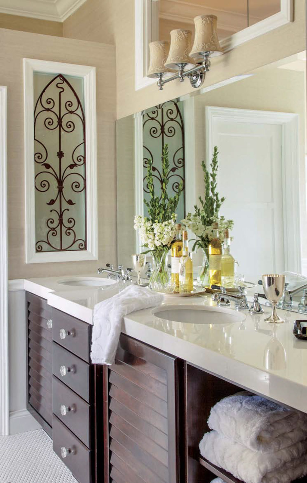 Double vanity bathroom sink area with dark wood drawers and tan accents on the wall and lighting with fresh flowers on the sink.