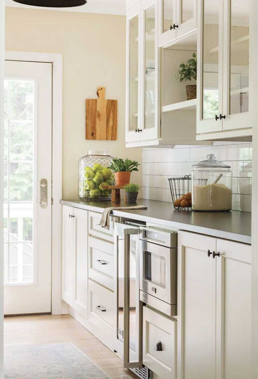 Creamy white kitchen, near a glass paneled back door letting in tons of light and small plants giving texture to the countertops.