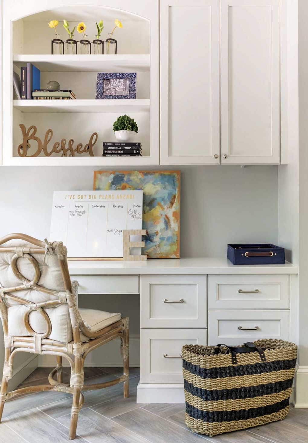 White cabinetry in a home office with a rattan styled chair next to a woven shoulder bag.