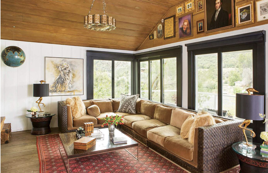 Living space with a wall of windows behind the sectional with a unique chandelier, lake house decor and a collection of portraits above the windows.