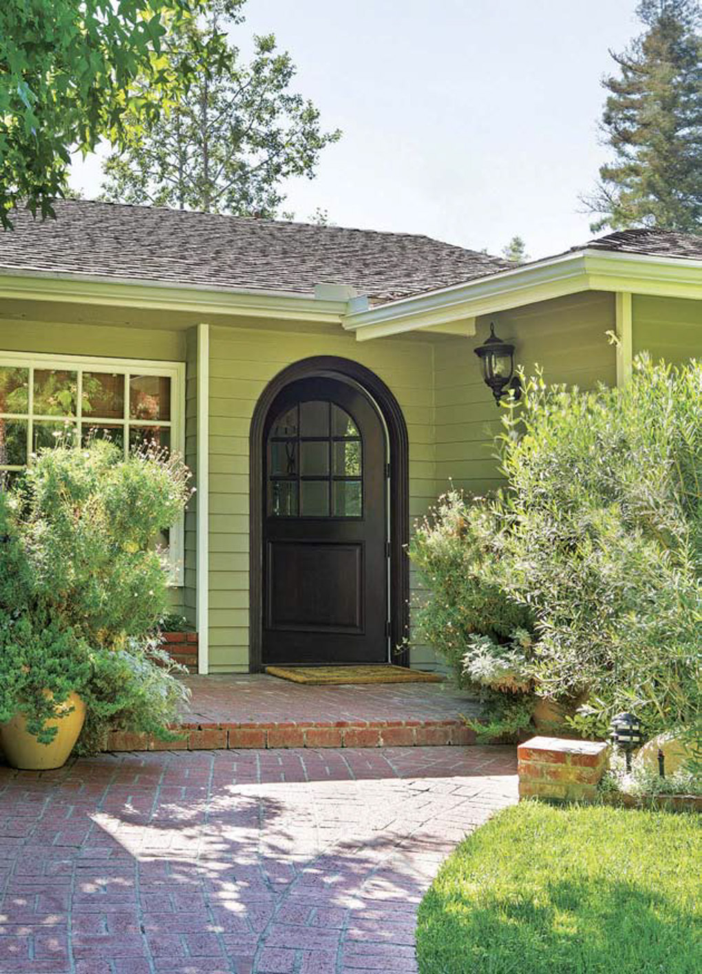 Brick paved front walkway up to a green home with an open rounded black front door.