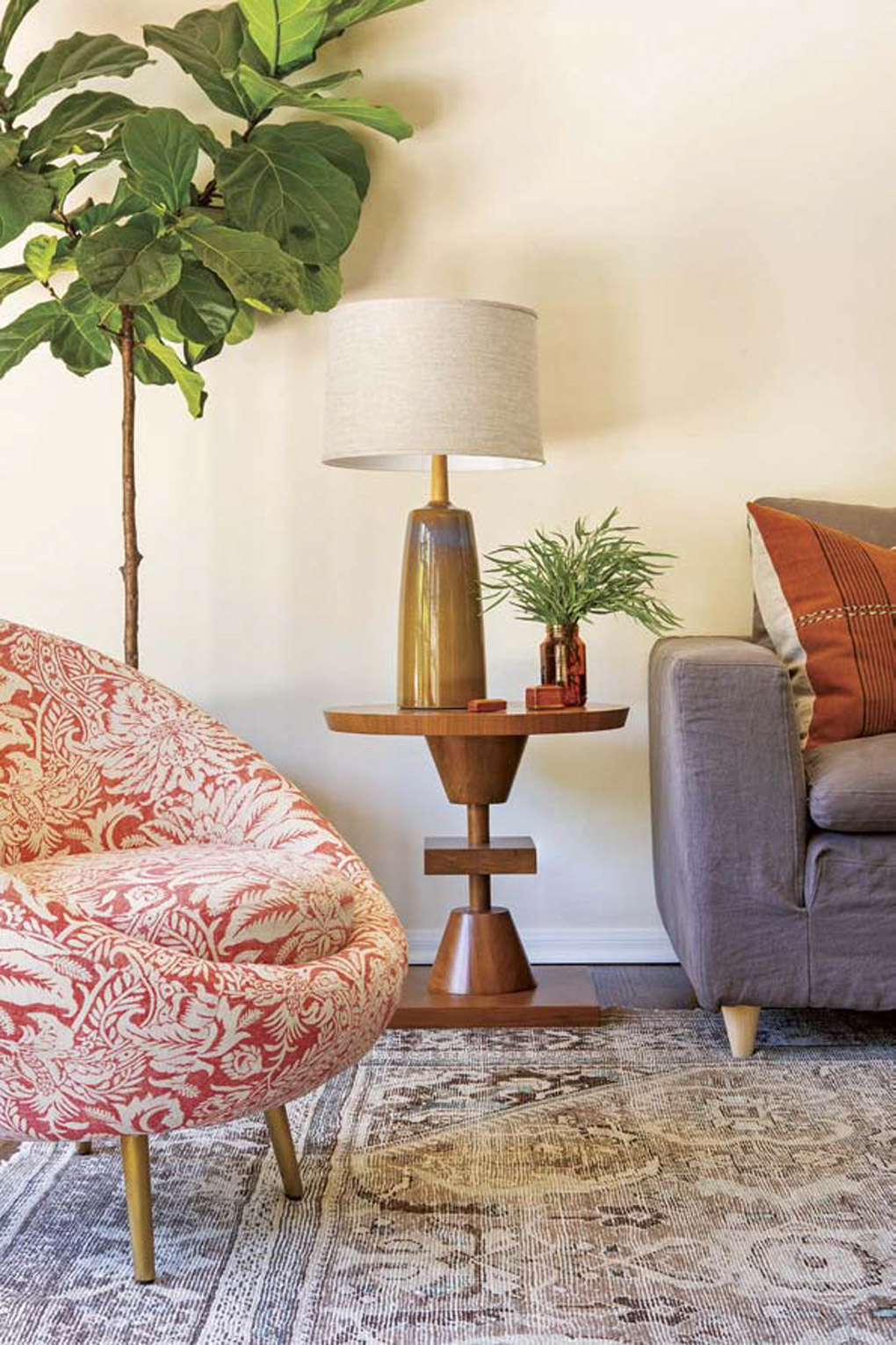Modern side table made of walnut topped with a lamp and fresh greenery, next to a barrel-rolled floral chair and a gray couch.