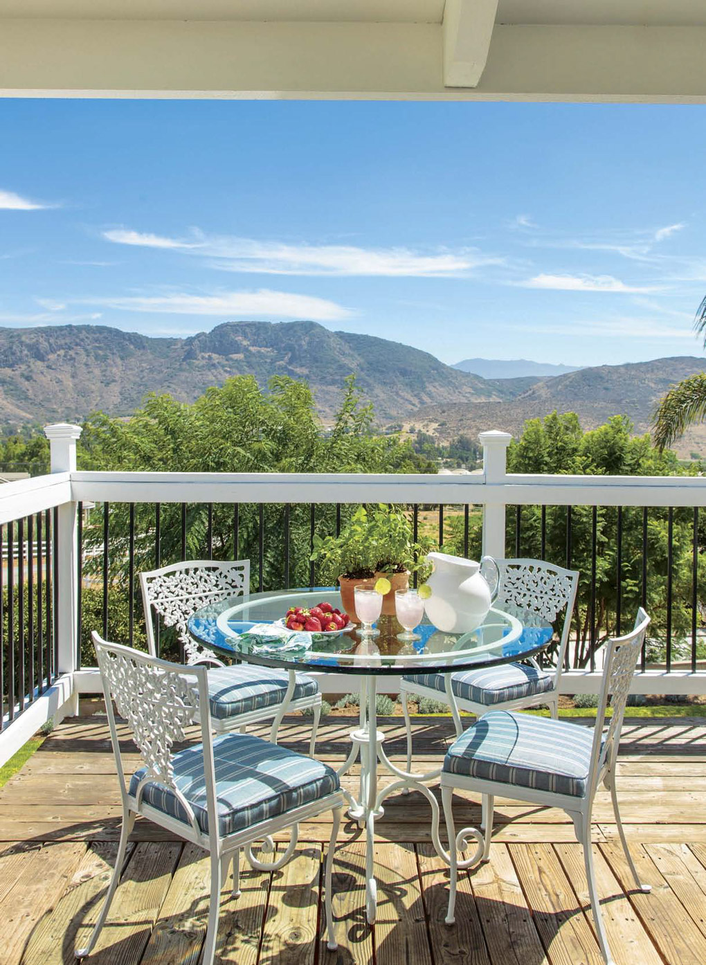 Wrap around deck with white metal dining bistro set arranged for a fresh breakfast with a view of expansive mountains.