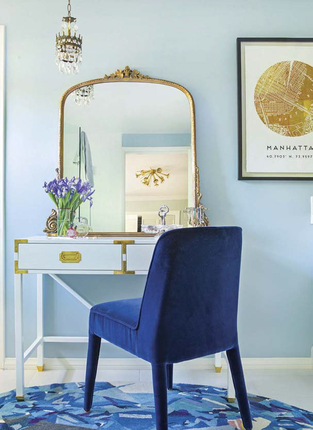 Bathroom vanity area with a gold accented mirror, hanging chandelier and a bright blue velvet chair.