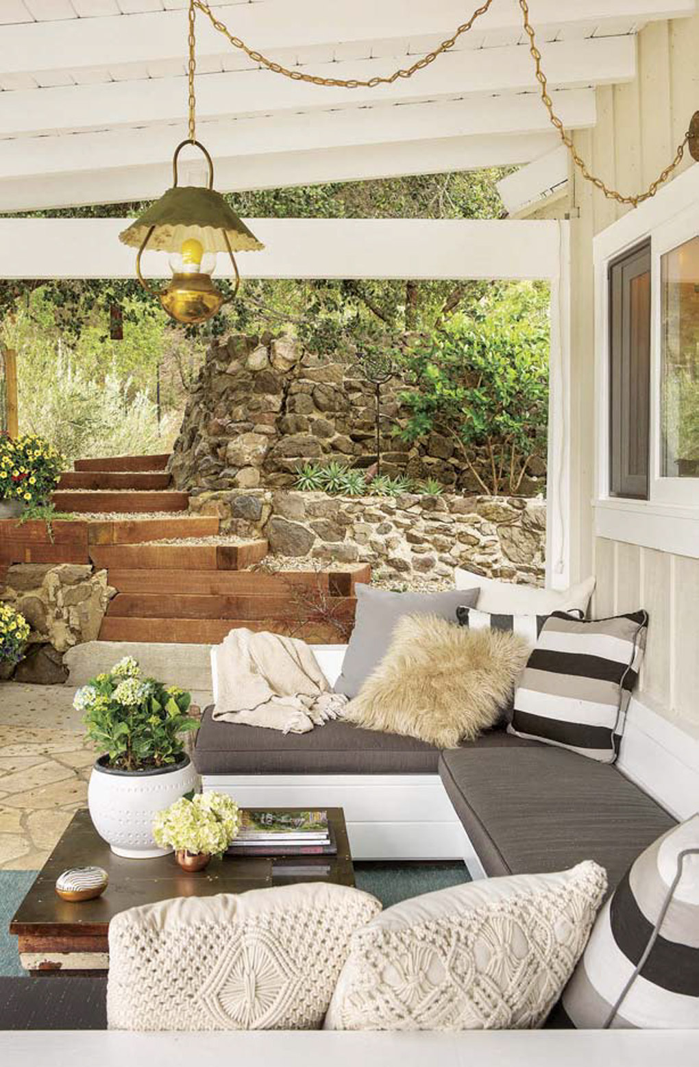 Hanging brass chained vintage light over an outdoor sectional with a vintage wooden coffee table and stone made walls with wooden steps in the background.