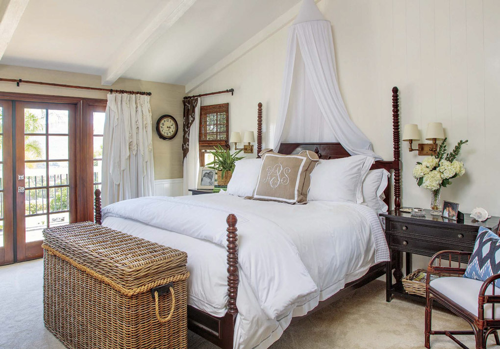 Master bedroom with a wooden carved four-poster bed topped with white linens and hanging mosquito netting as decoration.