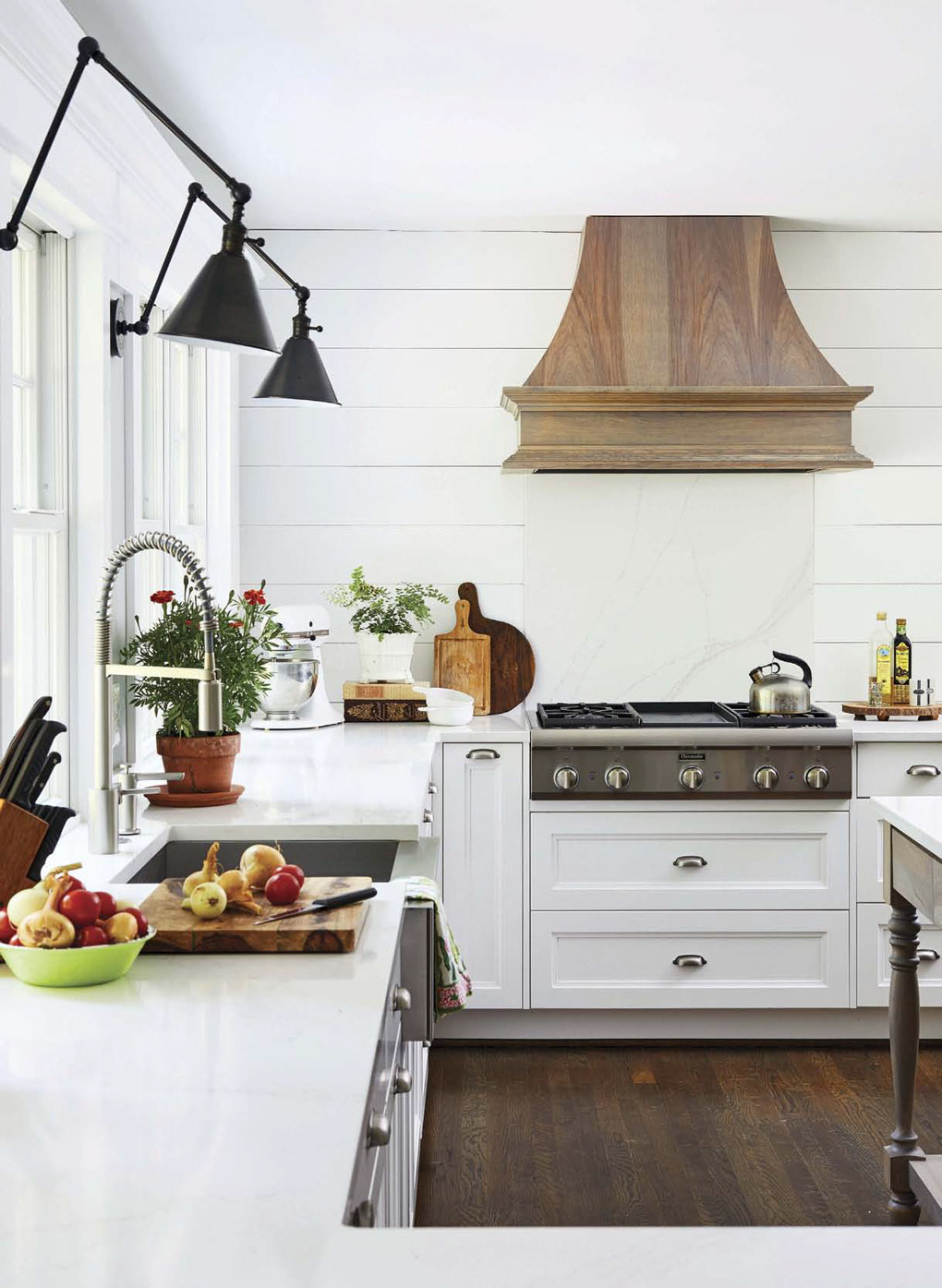 White kitchen with modern farmhouse lights above the sink and a custom wooden range hood.