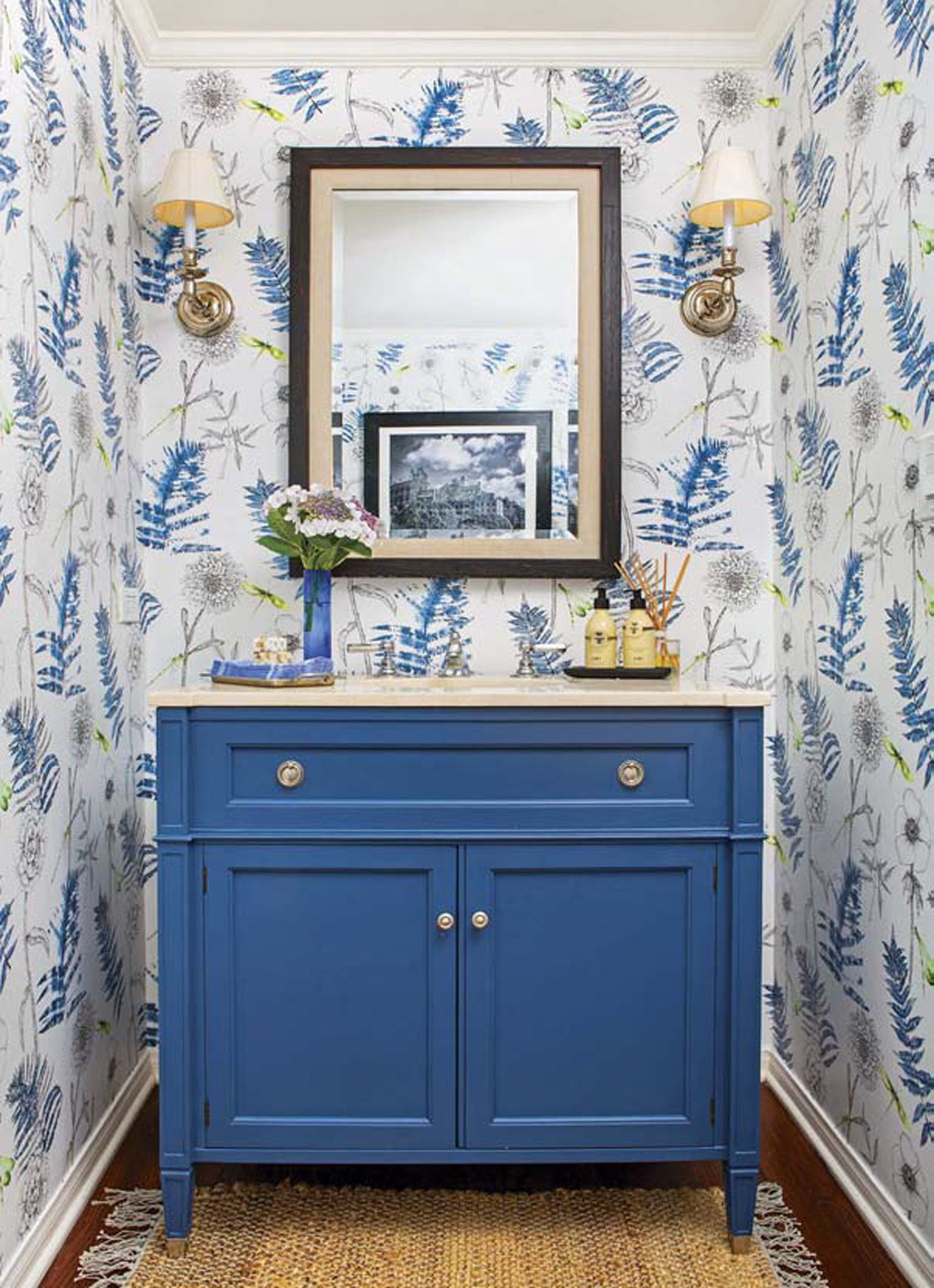 Powder bath with a bold blue vanity, surrounded by gold accents and floral wallpaper.