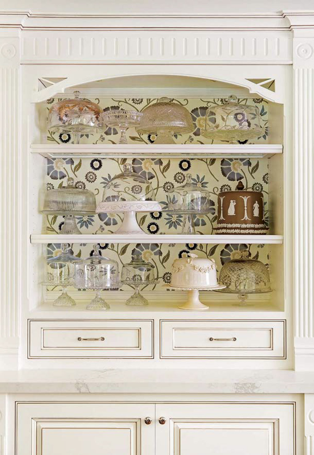 Cream colored accent cabinets with a custom display case filled with a collection of cake plates.
