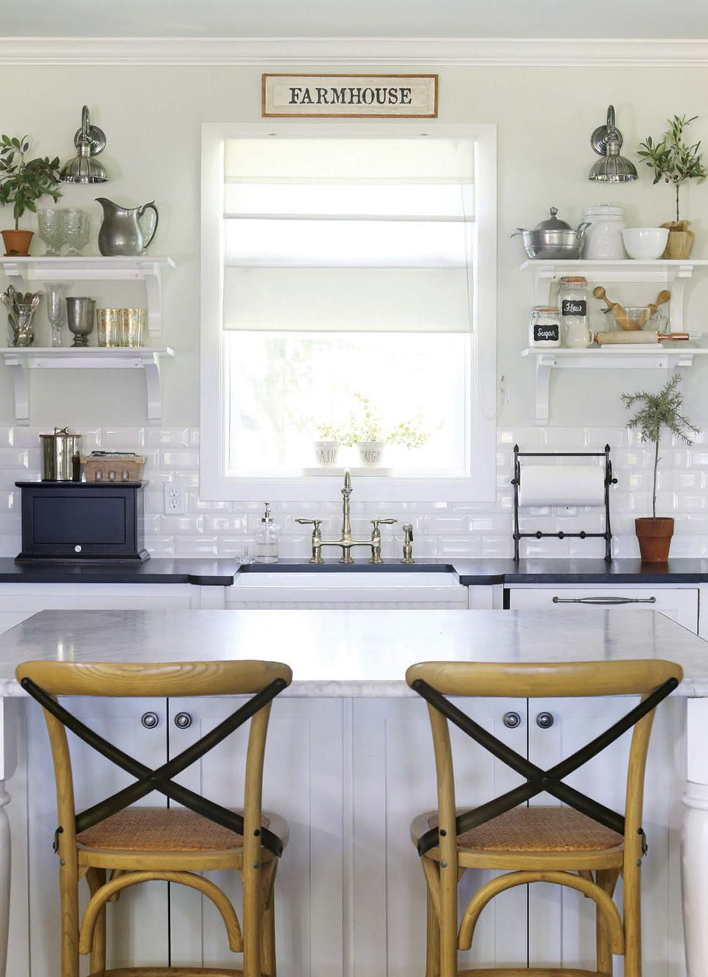 White kitchen renovation looking over two wooden barstools at the brightly lit center window flanked by white floating shelves.