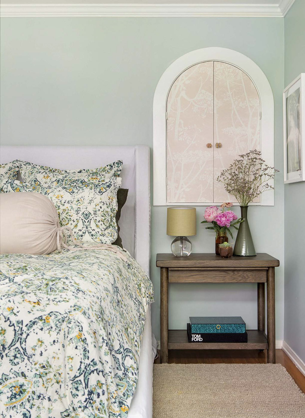 Floral bedspread with a wooden bedside table beneath a round topped storage cabinet in a California cottage master bedroom.