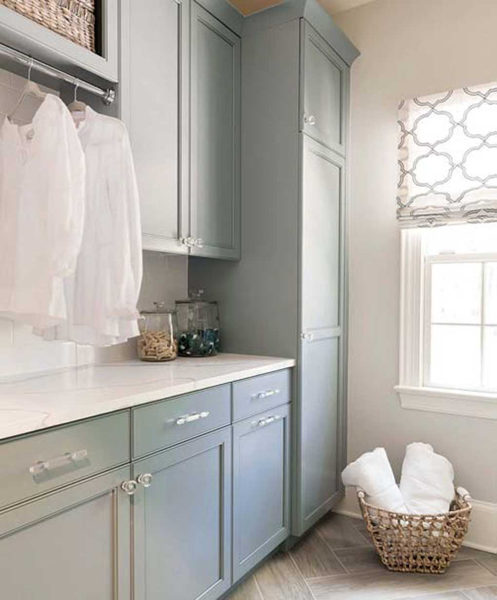 Clean and crisp laundry room with tile floor, blue cabinets and a wicker basket filled with white towels.