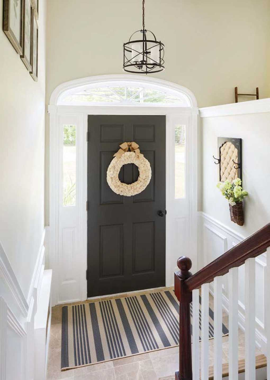 Large foyer with a hanging pendant lamp, beige floor tile and a black front door with a wreath.