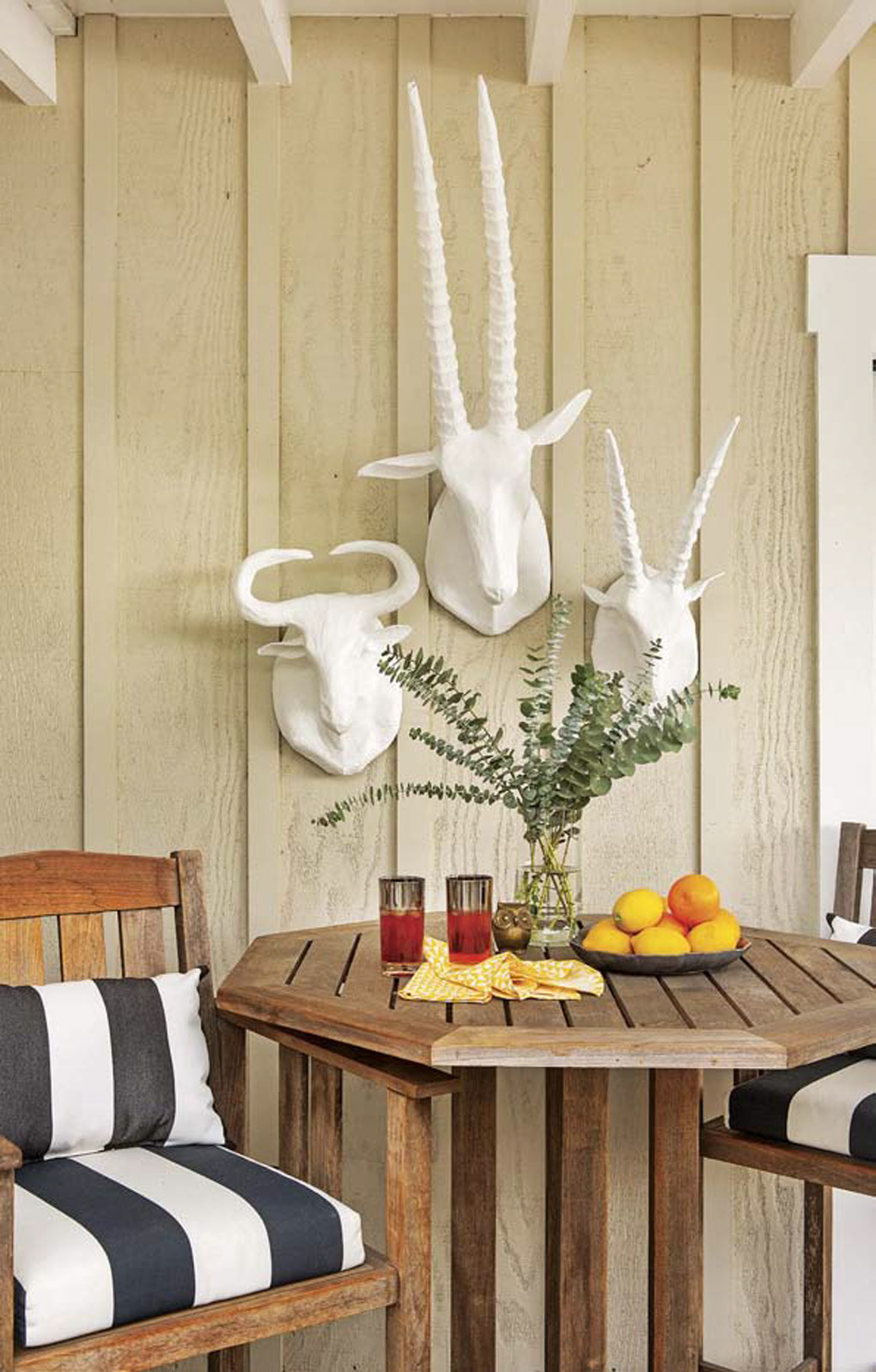 Outdoor teak bistro set with black and white striped cushions and set with a snack prepared in the table with white faux animal wall mounts on the wall.
