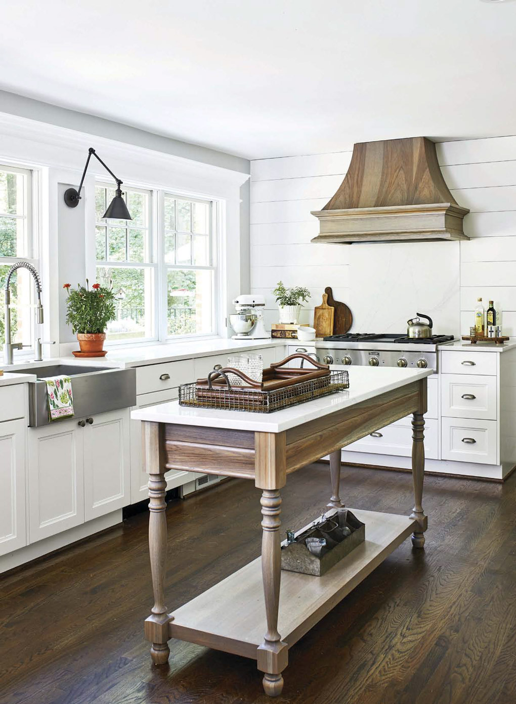 Custom designed island with turned wooden legs and all white kitchen counter and cabinetry in the background.