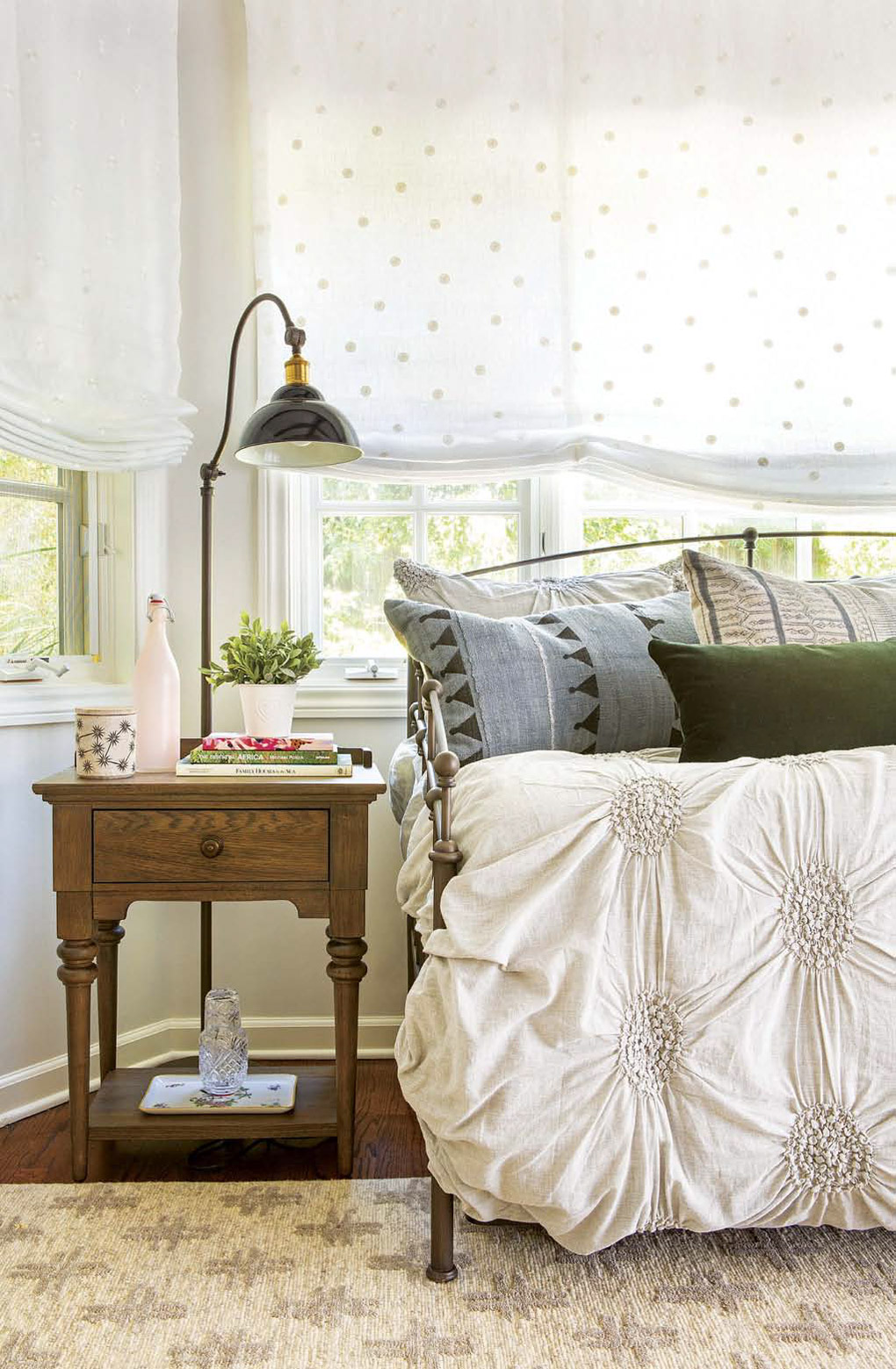 Guest room with an iron daybed next to an ornate bedside table topped with a lamp.