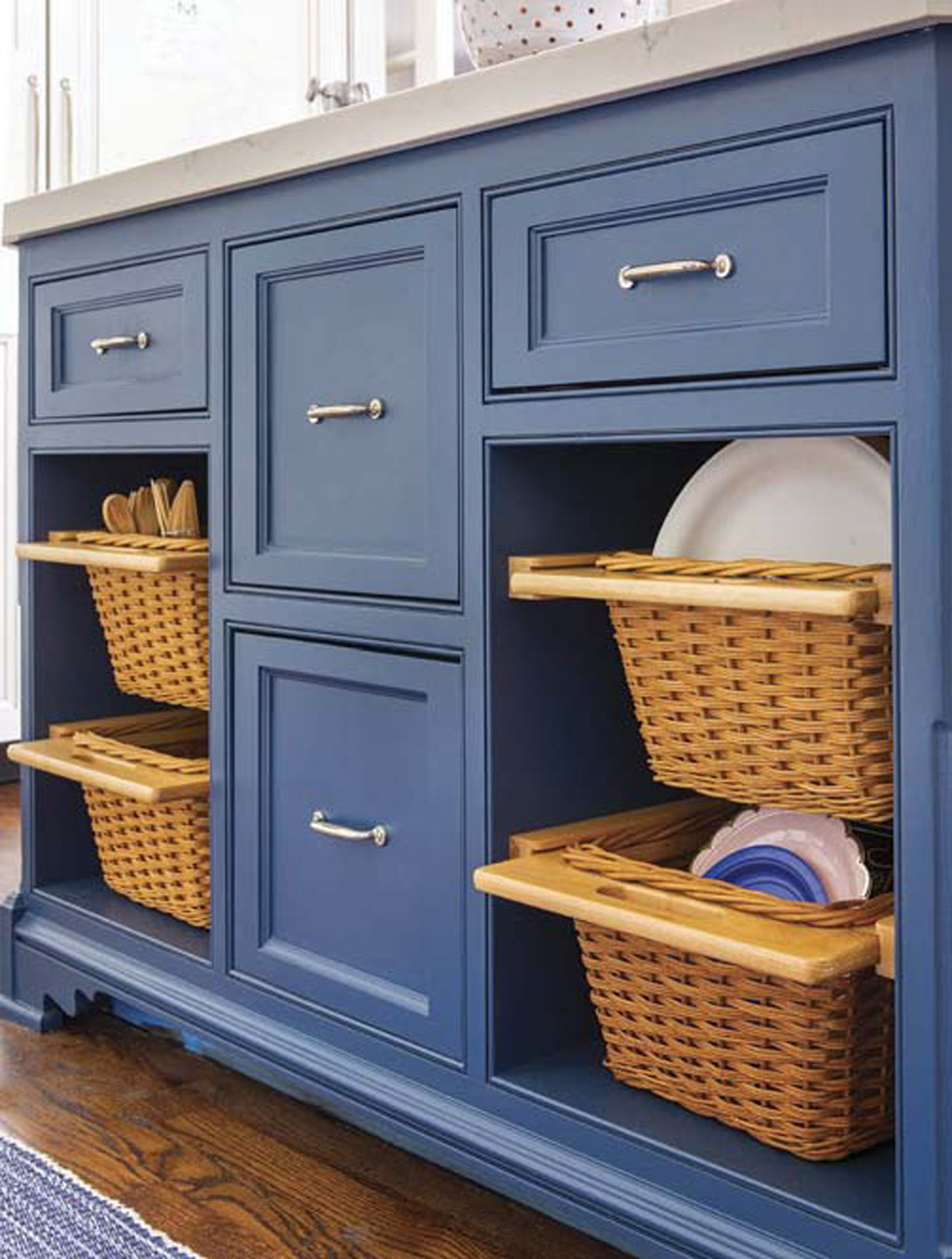 Blue lower cabinets with custom cutouts storing wicker storage baskets.