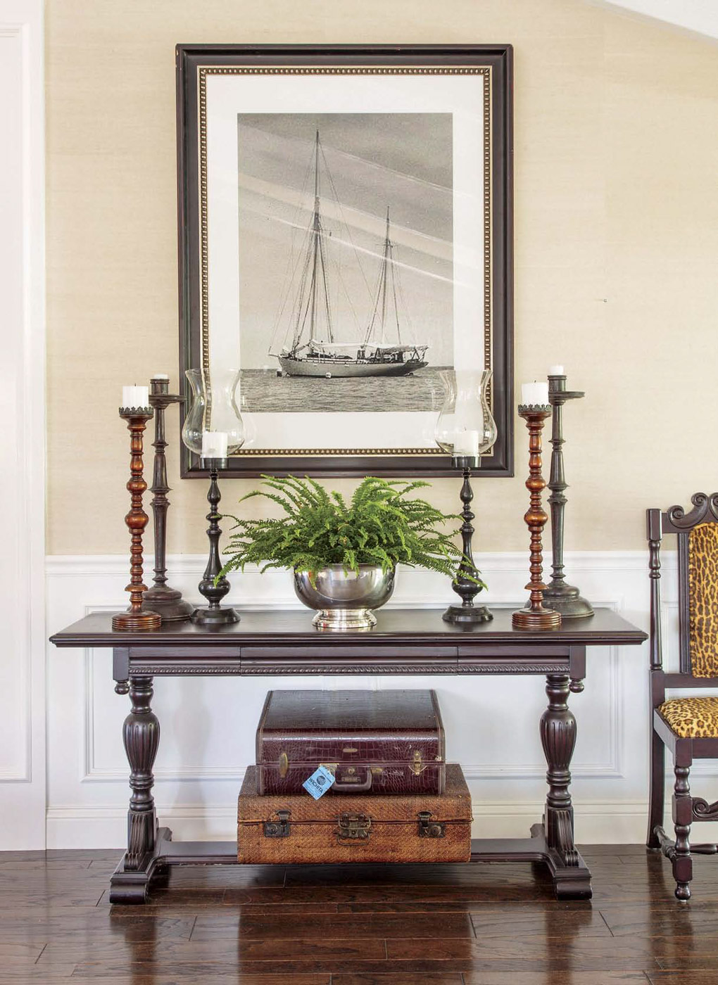 Antique wooden console in the entryway topped with tall candlesticks and a fern, also displaying vintage suitcases underneath.