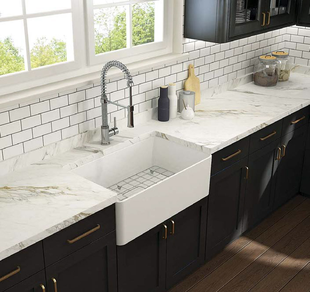 Farmhouse sink with marble counter tops in a kitchen with black cabinetry and brass handles.