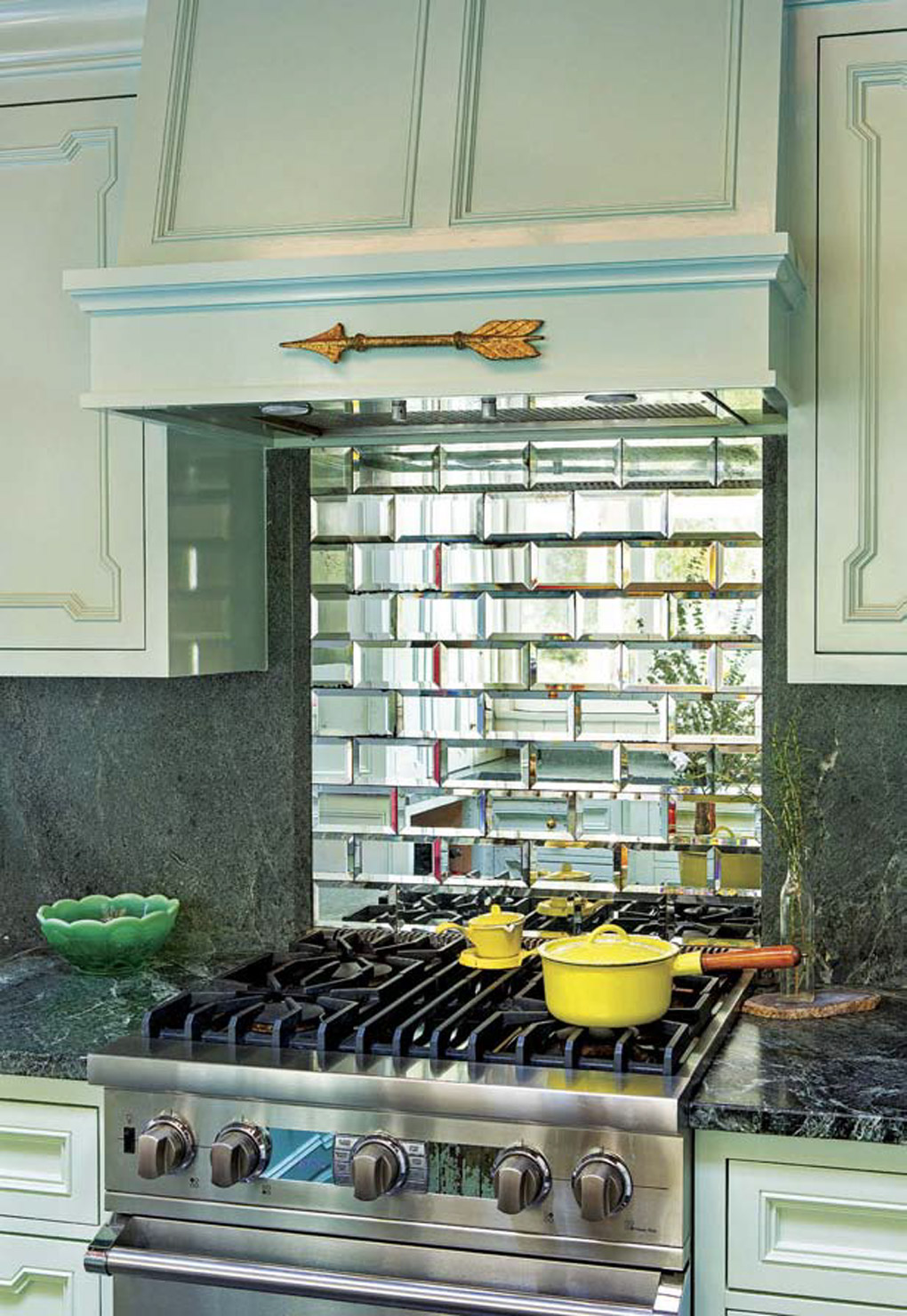 Small stainless steel range with a mirrored subway tile backsplash surrounded by light aqua colored cabinets.