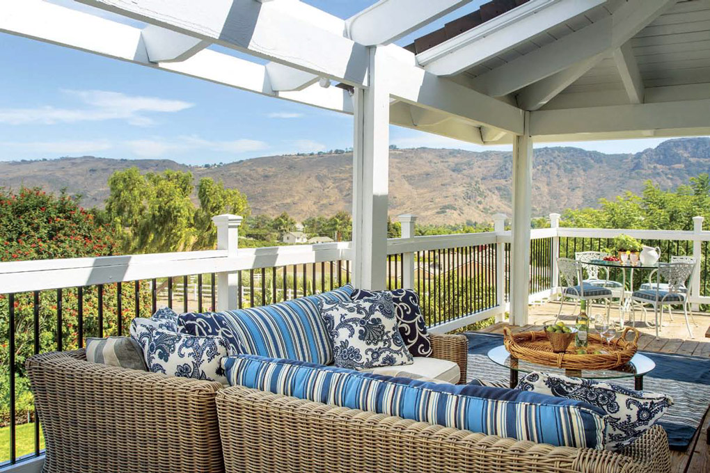Outdoor deck seating area with open pergola and rattan style sectional with blue accent cushions.
