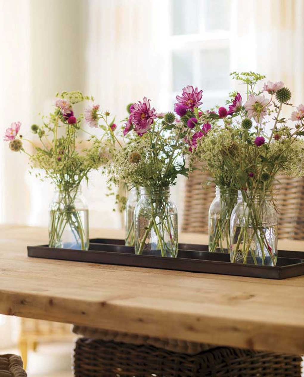 Mason jars filled with fresh-cut white and purple flowers placed together as a centerpiece on a farmhouse dining table.