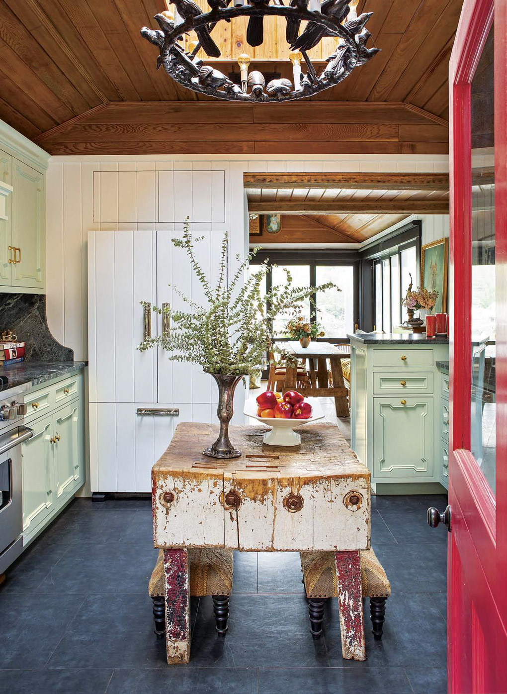 Bright red door opening into a cottage kitchen with rustic vintage island and light aqua cabinetry.